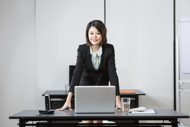 Attractive Chinese Business Woman leaning on her desk.