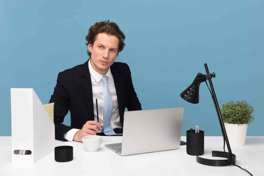Na foto aparece um homem vestido com terno, na cor preta, camisa branca e gravata azul clara. Ele está sentado em uma mesa de cor branca, com o olhar distante, pensando se deve fazer um curso de importação e se encaixa em algum perfil de importador. Na mesa, há um computador com a tela aberta, uma luminária na cor preta, com a luz desligada. Além disso, na mesa há também uma xícara de café, um vaso de planta e porta canetas.