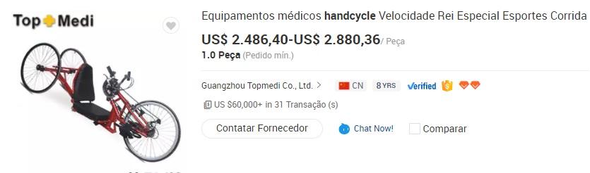 Na imagem vemos uma handbike, bike que se pedala com as mãos. O item é na cor vermelha, com assento na cor preta. O bicicleta possui três rodas, sendo um triciclo. Na imagem também vemos a variação de preços praticado pelo item no site Alibaba, de 2.489,40 a 2.880,36 dólares, entre outras informações.