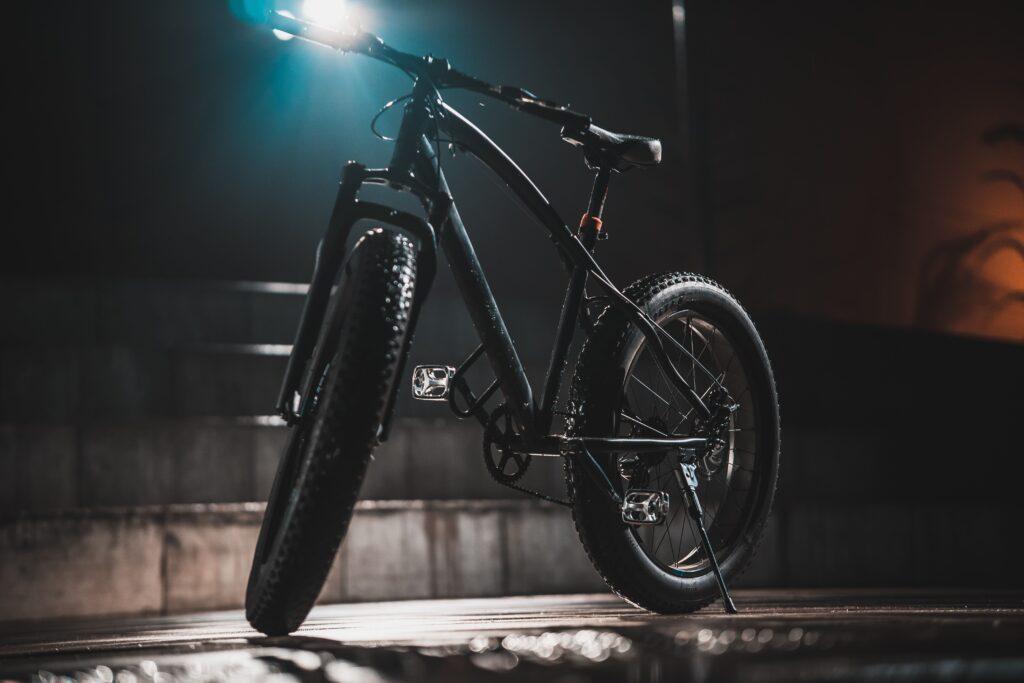 Modelo de bike que pode ser importada com a redução do imposto de importação de bicicletas. A foto mostra uma bicicleta na cor preta, com pneus grossos. Ela esta iluminada por um foco de luz, que está na parte superior da foto.