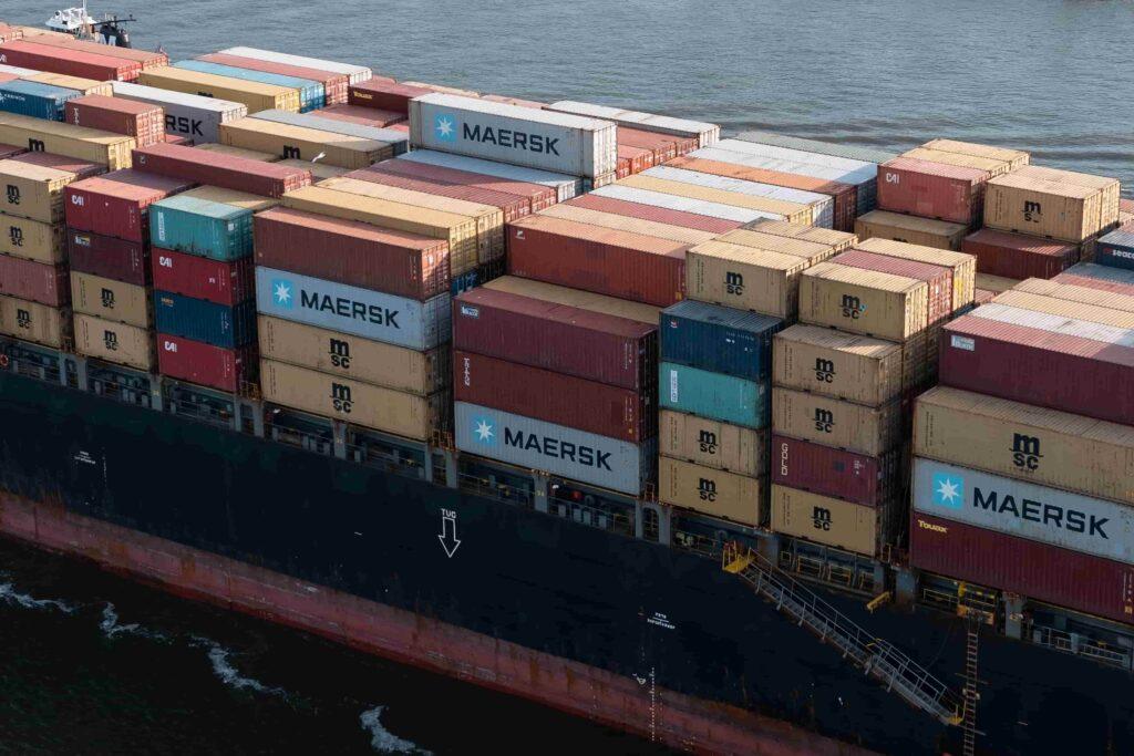 Imagem mostra cheio de containers de várias cores, em alto mar. Simula importação marítima a partir da China.
