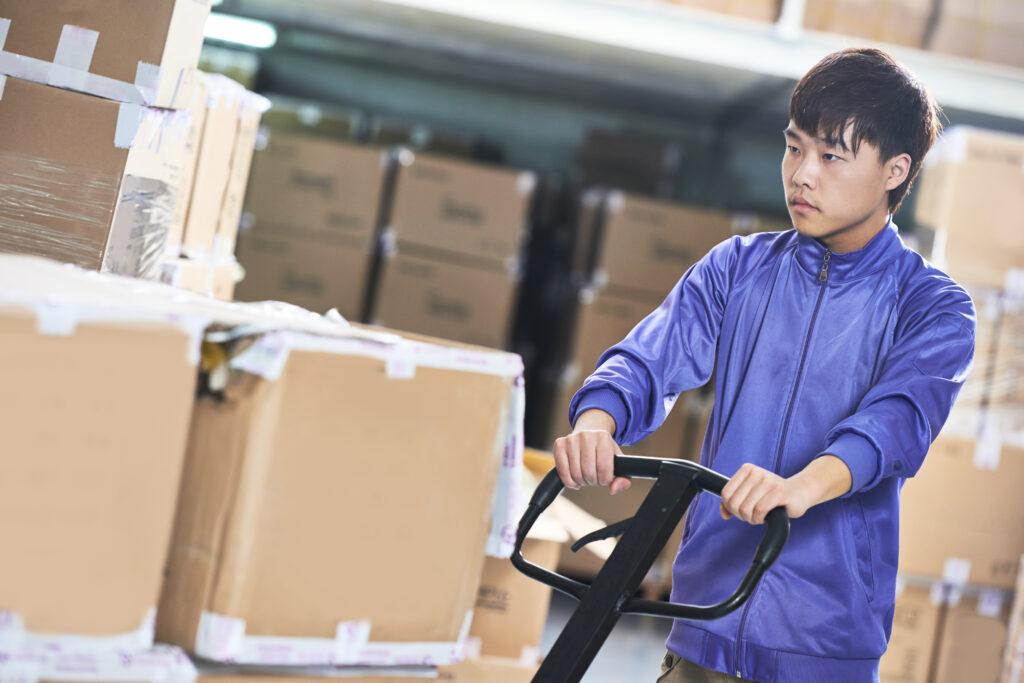 Imagem mostra homem de feições orientais, empurrando uma espécie de carro de carga. Ele está em um depósito repleto de caixas de vários tamanhos.