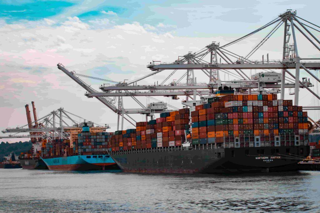 Imagem mostra três navios cargueiros parados em um porto. Eles estão abastecidos de containeires de produtos importados da china para revender.