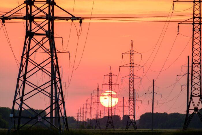 Torres de transmissão de energia em linha, com por do sol ao fundo.
